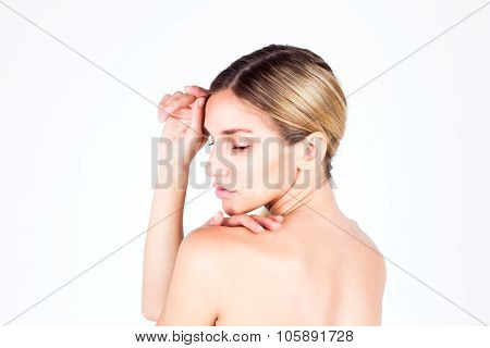 Young woman with beautiful skin and a naked back looking down and touching her forehead. Beauty conc