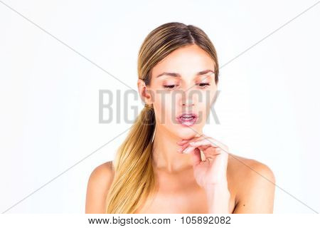 Clear skin. Beautiful woman looking down and touching her face.