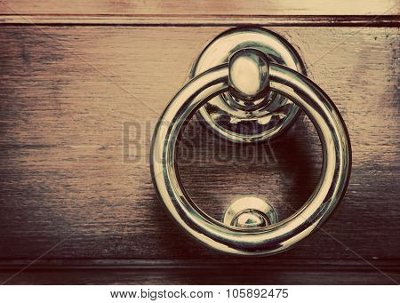 Antique golden door knocker on wooden door. Vintage, retro background