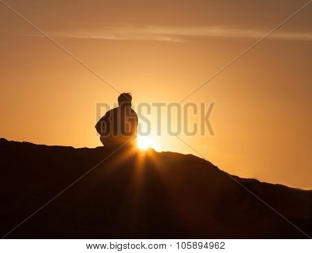 Silhouette of a lone man sitting at sunset