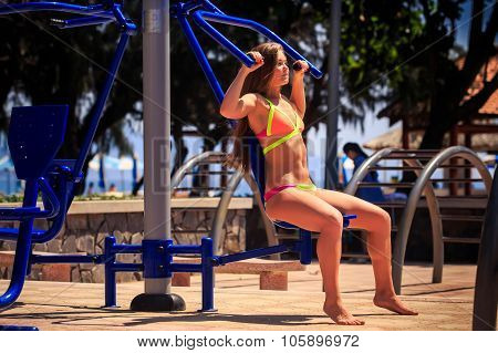 Blonde Girl In Bikini Sits On Weight Stack Simulator Near Beach
