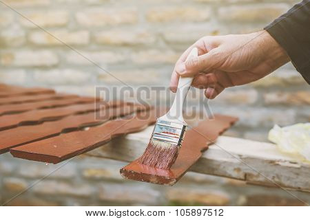 Man Painting Wooden Pickets For Hash Fence