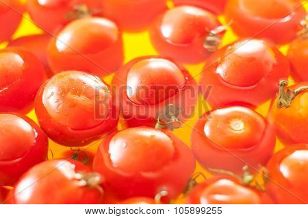 Very fresh tomatoes presented in water before canning or cooking, yellow background, soft focus