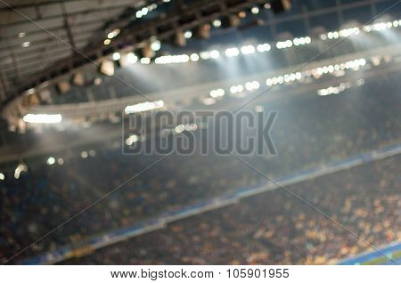 Blurred soccer stadium or ather sport arena at night with projector and stands full of people, fans,