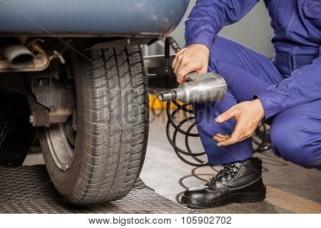 Cropped image of mechanic holding pneumatic wrench by car at garage
