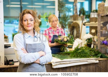 Portrait of confident female owner with worker in background at flower shop
