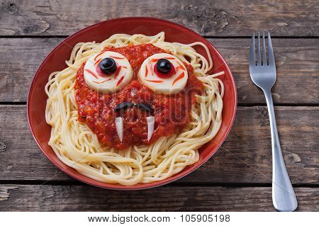 Halloween spaghetti face with big eyeballs fangs and moustaches in noodle dish, for celebration part