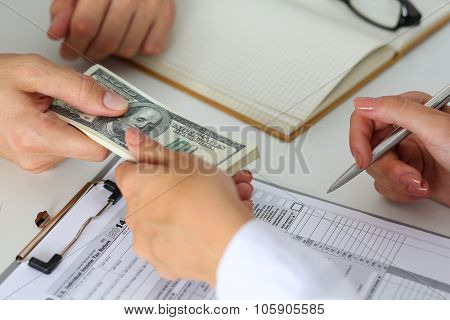 Male Hand Taking Or Giving Bunch Of Hundred Dollars Bank Notes