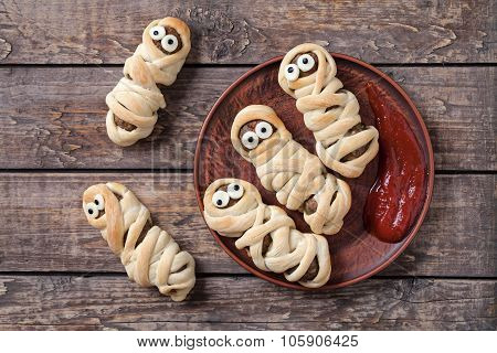 Funny sausage meatball mummies wrapped in dough scary halloween party decoration food on vintage woo