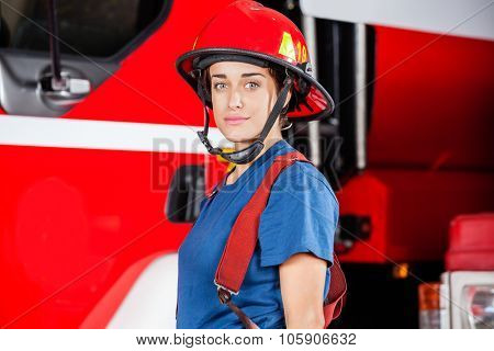Portrait of confident young firewoman wearing red helmet against firetruck at station