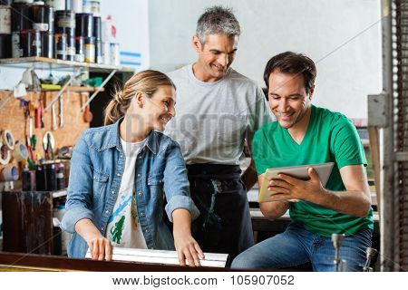 Happy male supervisor showing design on digital tablet to colleagues in paper factory
