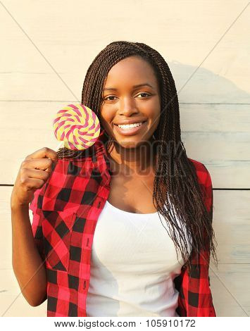 Portrait Beautiful Happy Smiling African Woman With Sweet Lollipop, Wearing A Red Checkered Shirt In