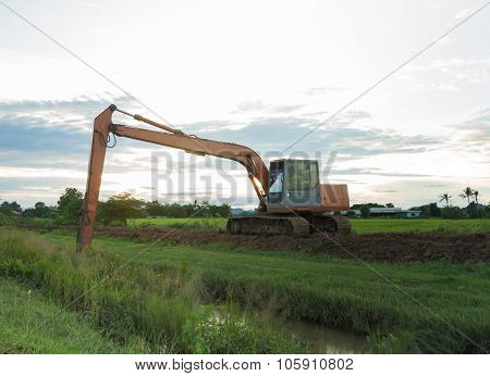The Big Backhoe Excavator Machine In The Green Rice Field