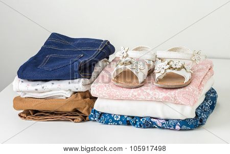 Stack Of Clean Baby Clothes In White Wardrobe