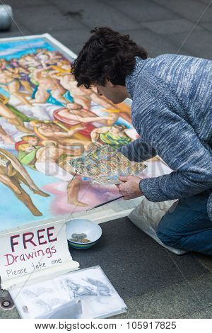 SYDNEY, AUSTRALIA - SEPTEMBER 14, 2014: An unknown man paints a very big fresco in the middle of Pitt Street. He is giving away for free some of his drawings to pedestrians and tourists.