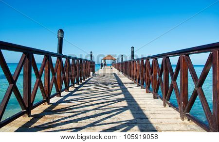 Long Wooden Dock With Fence, Stretching Into The Sea