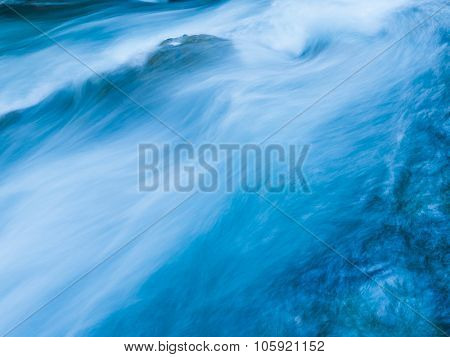 Detail of a beautiful Marian Creek. Beautiful abstract background of a blue flowing water taken with a long exposure