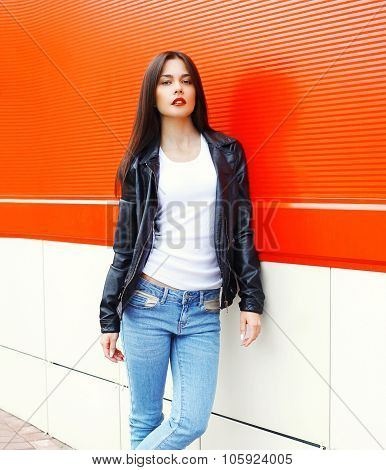 Fashion Beautiful Brunette Woman Wearing A Rock Black Leather Jacket Posing In City Against Red Back