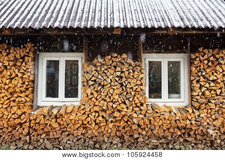 Windows of a traditional country cottage house with firewood logs during snowfall.
