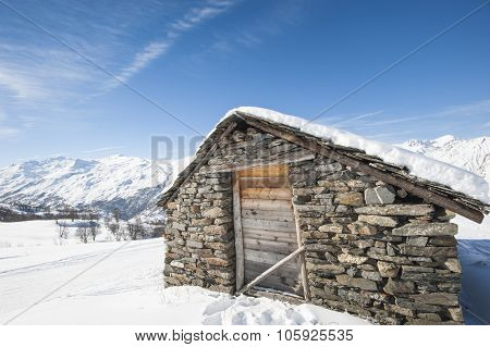 Isolated Mountain Hut In The Snow