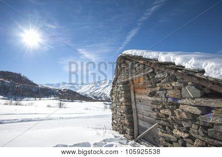 Isolated Snowy Mountain Hut In The Sun