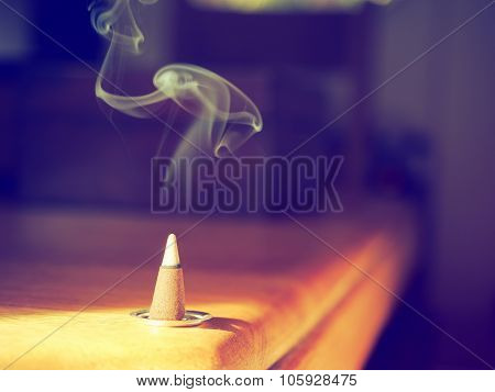 Smoking incense cone on a table with smoke in vintage style