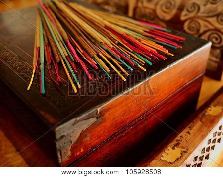 Coloured Incense sticks on a Rustic Wooden Box