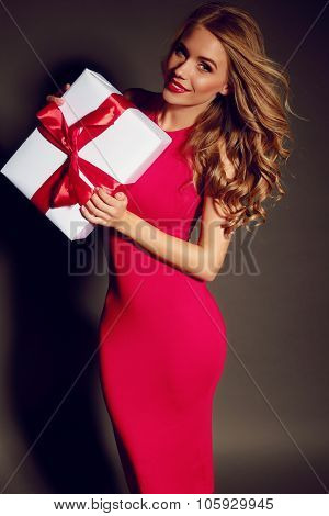 Sexy Girl Holding A Box With A Gift And Posing In Studio