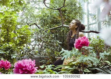 young adorable pretty girl with pigtails hairstyle smiling outside among trees