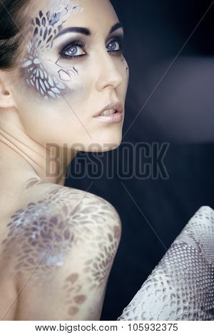 fashion portrait of pretty young woman with creative make up like a snake, fashion victim with pytho