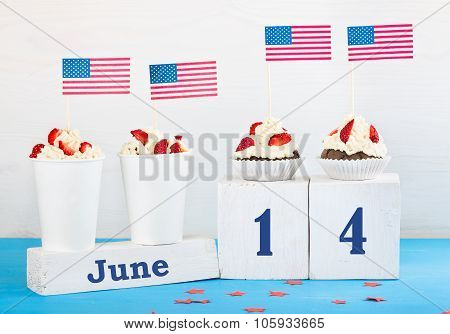Greeting card on the day of the flag of America two cupcakes two desserts with cream strawberries perpetual calendar with the words June 14 on a white and blue background