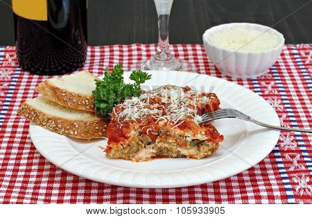 One Serving Of Eggplant Parmesan With Sides Of Wine And Parmesan Cheese.