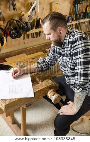 Carpenter plans projects and takes notes on drawing in workshop