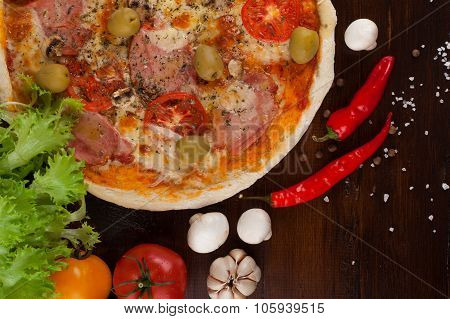 Homemade pizza with ham, cheese and olives.
