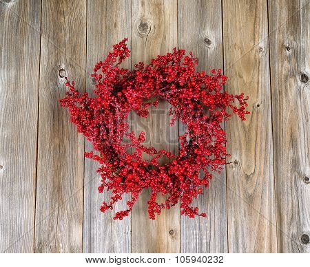 Red Holly Berry Wreath On Aged Wooden Boards