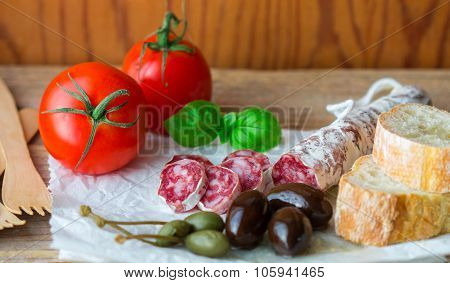 A set of cold appetizers - smoked sausage, bread, olives, capers, tomatoes, Basil