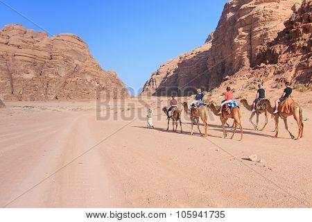 Wadi Rum, Jordan - March 24,2015: Tourists Riding Camels At Sunset In The Wadi Rum Desert, Jordan