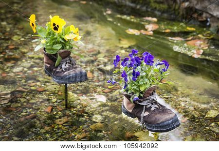 old boots converted in flowerpots for decoration on a water stream
