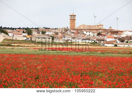 Classic Rural Spain - Red Poppy Field And Small Town With  Power Generators