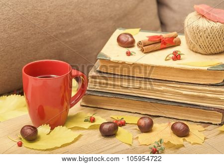 Autumn still-life with a cup of tea and old books.