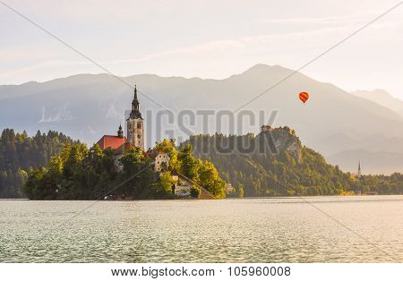 Catholic Church In Bled Lake And Bled Castle, Slovenia With Hot Air Balloon Flying At Sunrise