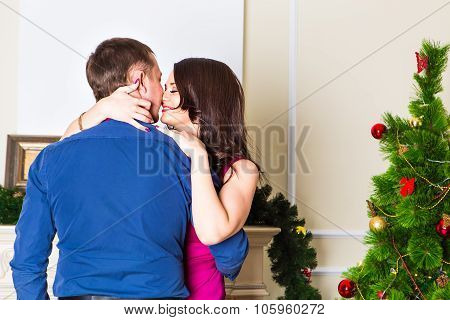 Young happy couple near  a Christmas tree