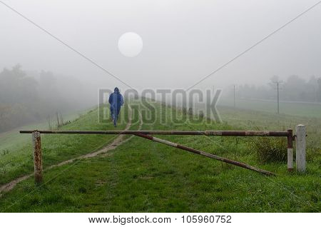 Young Man Jogging In Nature On Cold Misty Autumn Day