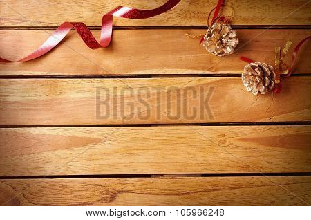 Red Ribbon And Pinecone Christmas Decoration On Wooden Table Top