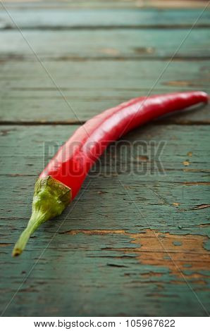 Red hot chilli peppers on wooden background