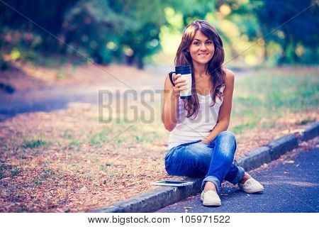 Happy young woman by a coffee cup sitting on earth and uses a plane-table