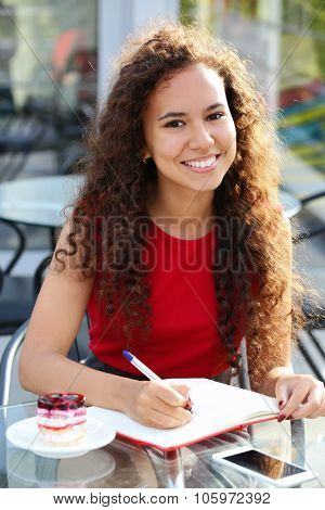 Young smiling  woman in red dress makes notation at the summer terrace