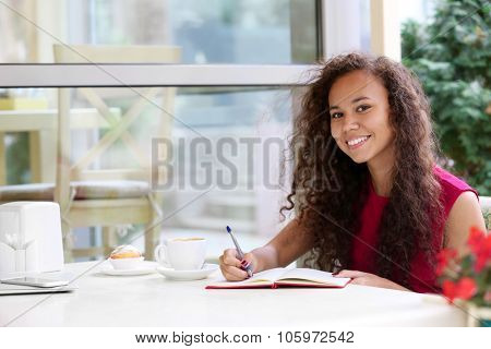 Young smiling pretty woman makes notation at the restaurant's terrace