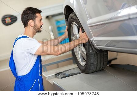 handsome mechanic changing a tire in workshop