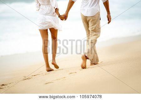 Back view of a barefoot couple walking